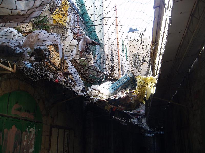 Hebron - الخليل : Trash thrown from above by the settlers on the Palestinian below. This net was erected to limit the damage. Residents are constantly harassed and terrorized by the Israeli soldiers and settlers.