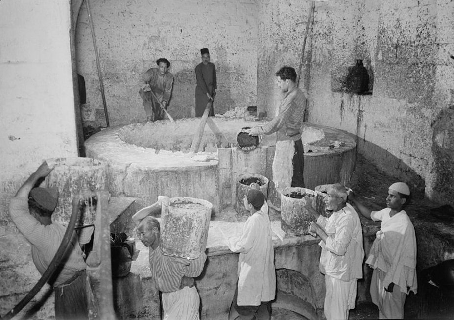 Nablus - نابلس : NABLUS - The Soap Factory. The boiling pot liquid soap being carried to stock room, 1940 (Matson collection)