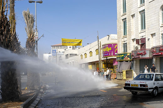al-Ram - الرامّ : Demonstrators stand just out reach of an Occupation water cannon in the main street of Ar Ram.