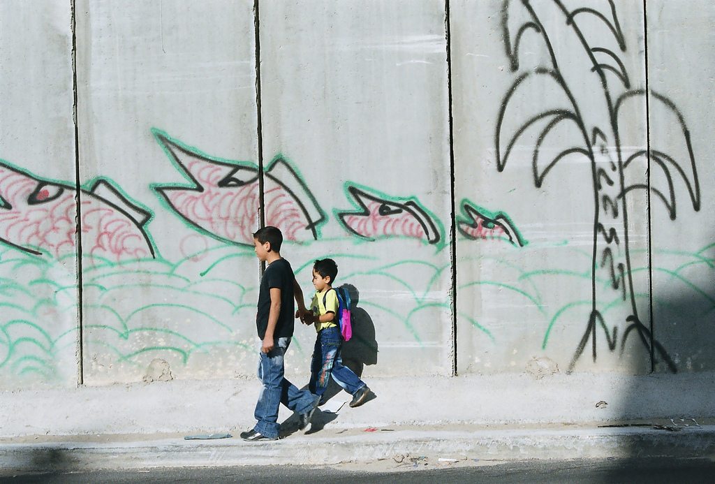 al-Ram - الرامّ : Ar-Ram checkpoint. Palestinian children walking by the graffitied wall at Ar-Ram Checkpoint.