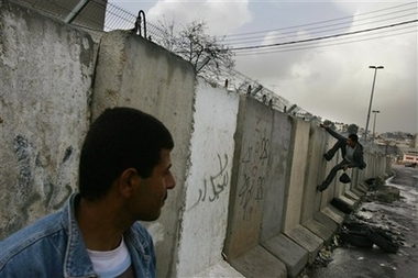 al-Ram - الرامّ : A Palestinian worker climbs over a section of Israel's separation barrier from the Palestinian village of Al-Ram towards Jerusalem, Sunday, Feb. 18, 2007.