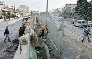 al-Ram - الرامّ : Palestinians cross a section of Israel's separation barrier from the Palestinian village of Al-Ram towards Jerusalem, Sunday, Feb. 18, 2007.