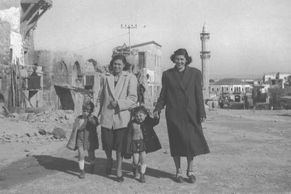 Jaffa - يافا : New Jewish refugees strolling in Jaffa soon after occupation in 1949. Note the Big Mosque (al-Mashid al-Kabir) is in the background. Soon after occupation, Jaffa was settled with new European Jewish refugees.