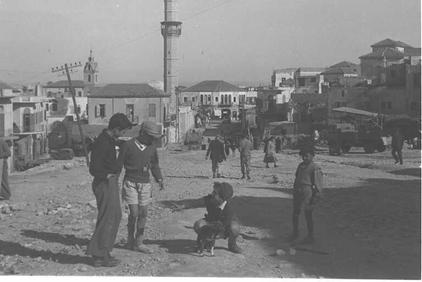 Jaffa - يافا : New Jewish refugees strolling in Jaffa soon after occupation in 1949. Note the Big Mosque (al-Mashid al-Kabir) and the clock tower is in the background. Soon after occupation, Jaffa was settled with new European Jewish refugees