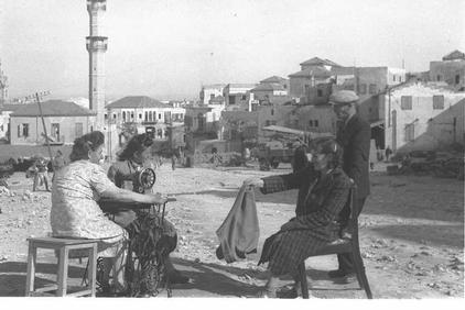 Jaffa - يافا : New Jewish refugees strolling in Jaffa soon after occupation in 1949. Note the Big Mosque (al-Mashid al-Kabir) and the clock tower is in the background. Soon after occupation, Jaffa was settled with new European Jewish refugees. (#2)