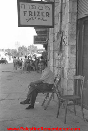al-Ramla - الرمله : A Jewish immigrant outside a looted barbershop (1962)